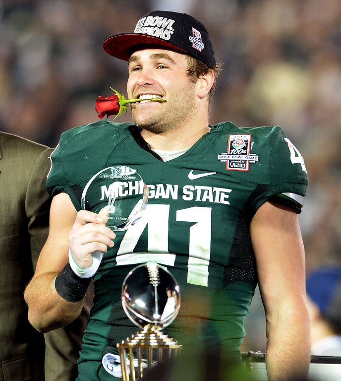 . Michigan State\'s Kyler Elsworth celebrates as he holds a rose in his mouth after defeating Stanford 24-20 during the 100th Rose bowl game in Pasadena, Calif., on Wednesday, Jan.1, 2014. 