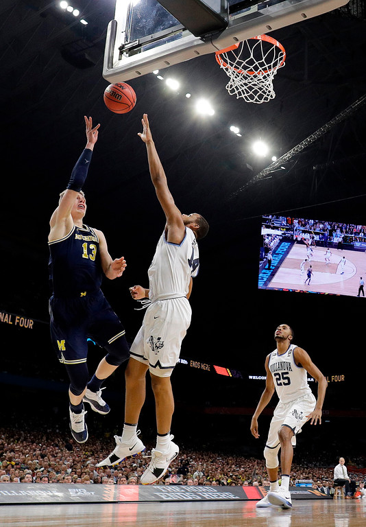 . Michigan\'s Moritz Wagner (13) shoots over Villanova\'s Omari Spellman (14) during the first half in the championship game of the Final Four NCAA college basketball tournament, Monday, April 2, 2018, in San Antonio. (AP Photo/David J. Phillip)