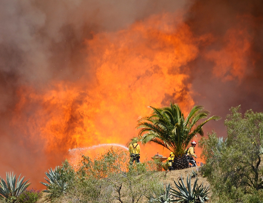 . Firefighters battle huge flames during the second day of the Springs Fire in the mountain areas of Ventura County CA.  May 3, 2013. A fierce, wind-whipped brush fire spread on Friday along the California coast northwest of Los Angeles, threatening several thousand homes and a military base as more than 1,100 dwellings were ordered evacuated and a university campus was closed. May 2,2013. Ventura County California.  Photo by Gene Blevins/LA Daily News