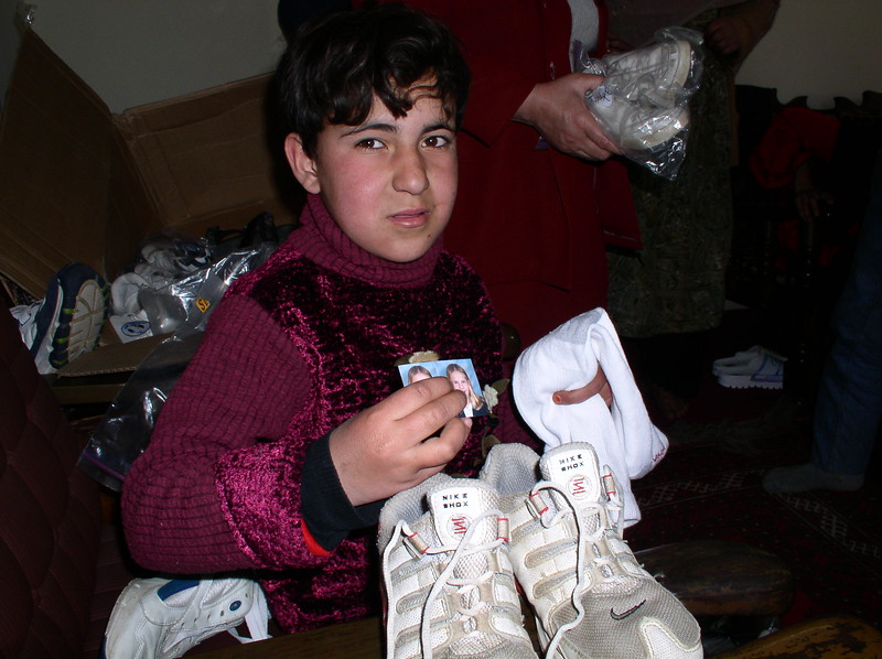 Another shoe recipient holding 2 pictures.