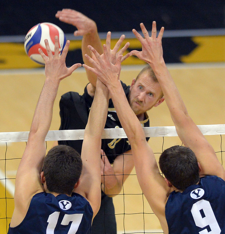 . LBSU\'s Dalton Ammerman hits around the blocks of BYU\'s Joseph Grosh, left, and Tyler Heap in Long Beach, CA on Friday, March 7, 2014 #2 BYU vs #3 Long Beach State men\'s volleyball at Walter Pyramid. (Photo by Scott Varley, Daily Breeze)