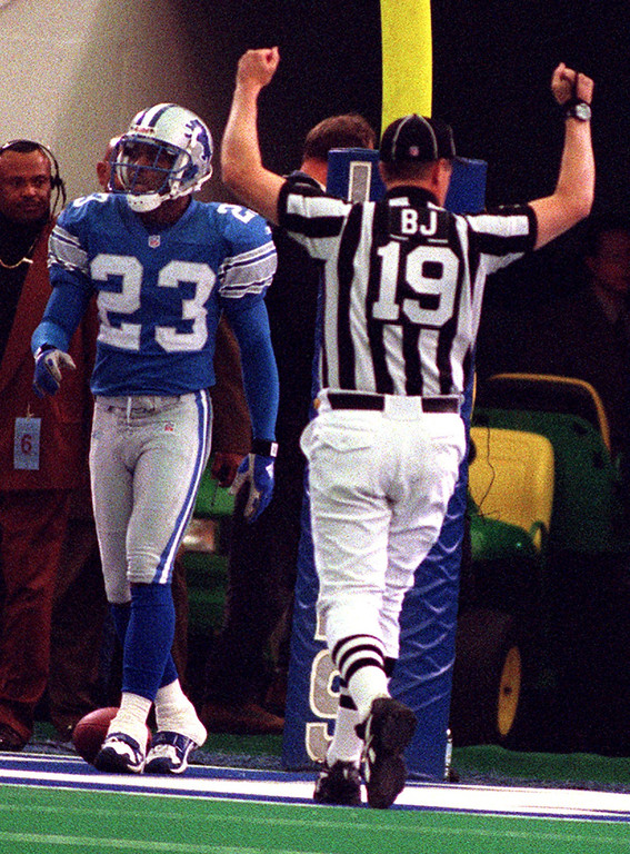 . Detroit Lions Cornerback Terry Fair walks away stunned as the offical signals a Cincinnati touchdown by Bengal Corey Dillon who ran all the way down the field during the first minute of play to make the score.
