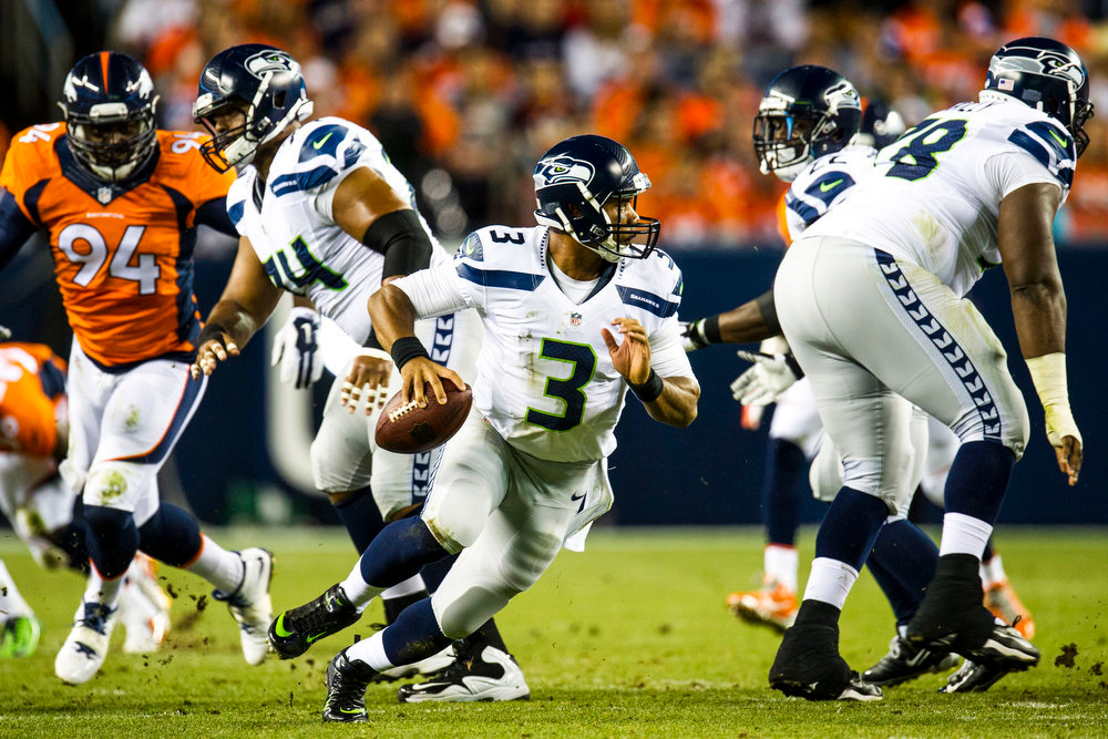 . Russell Wilson (3) quarterback of the Seattle Seahawks scrambles out of the pocket during second quarter action of a preseason game between the Denver Broncos and the Seattle Seahawks at Sports Authority Field at Mile High on Thursday, August 07, 2014 in Denver, Colorado.  (Photo by Kent Nishimura/The Denver Post)