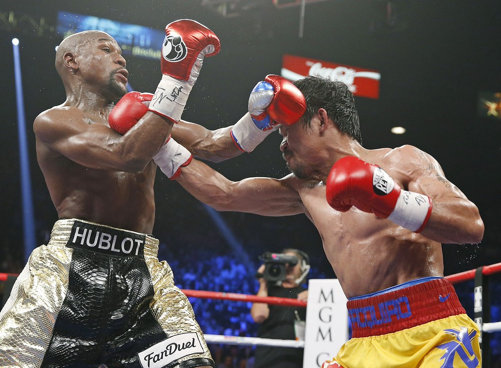 . Manny Pacquiao, from the Philippines, right, connects with a right to the head of Floyd Mayweather Jr., during their welterweight title fight on Saturday, May 2, 2015 in Las Vegas. (AP Photo/John Locher)