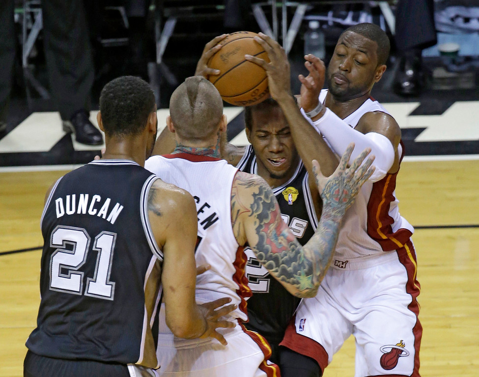 . Miami Heat guard Dwyane Wade (3) and forward Chris Andersen (11) apply pressure on San Antonio Spurs forward Kawhi Leonard (2) in the first half in Game 4 of the NBA basketball finals, Thursday, June 12, 2014, in Miami. (AP Photo/Wilfredo Lee)