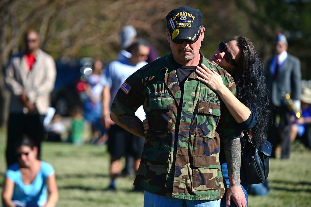 """. Joy Rose caresses the face of her boyfriend former army Sgt. Mike Gomez during the 36th annual Remembrance ceremony of Veteran\'s Day at Fort Logan Cemetery in Lakewood, CO  on November 11, 2013. The day was marked with a 21 gun rifle salute, \""""Echo taps\"""" played by buglers and the release of white birds of freedom.  The benediction was given by Jackie Newlander.  (Photo By Helen H. Richardson/ The Denver Post)"""