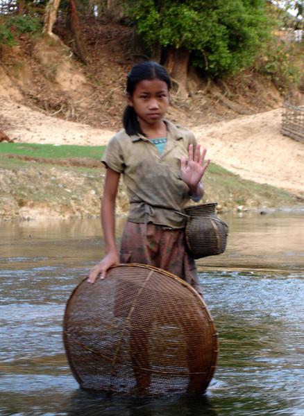 girl net fishing along a river, Laos