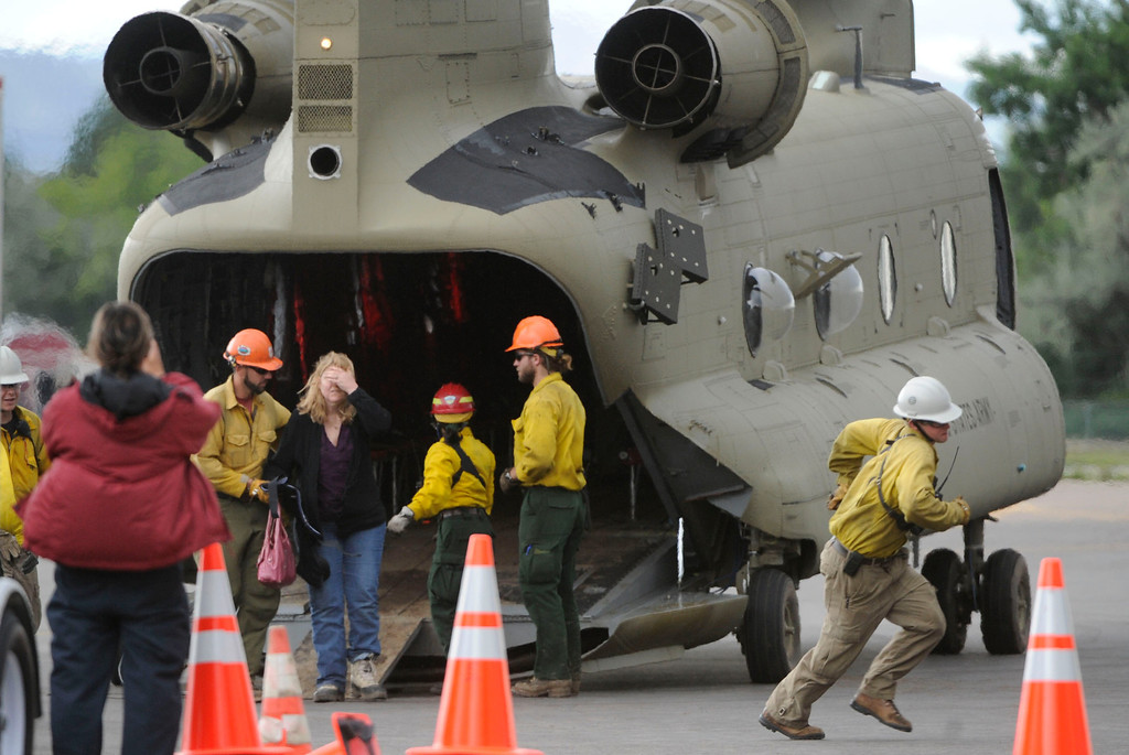 . BOULDER, CO - SEPTEMBER 13: A Jamestown evacuee is helped off a chinook helicopter at the Boulder Municipal Airport Friday afternoon, September 13, 2013. (Photo By Andy Cross/The Denver Post)