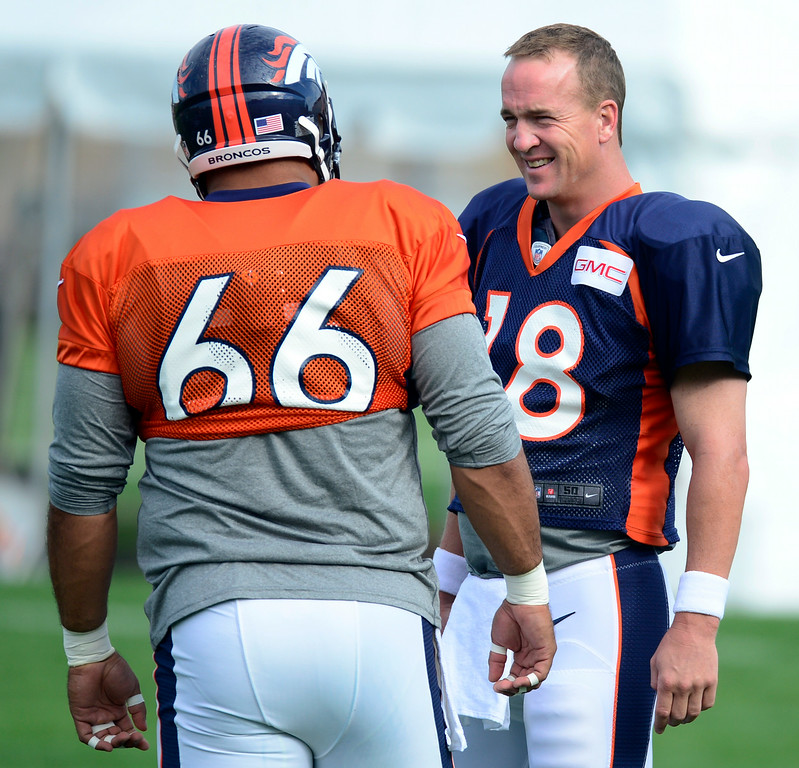 . Quarterback Peyton Manning (18) talks with center Manny Ramirez (66) before the start of drills on Saturday. The Denver Broncos football team hold their workouts for the team during mini-camp at Dove Valley in Centennial on Saturday, July 26, 2014. (Photo by Kathryn Scott Osler/The Denver Post)