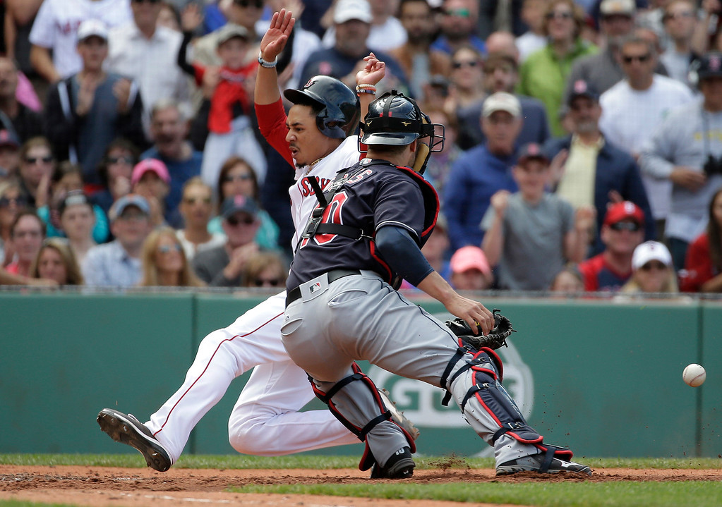. Boston Red Sox\'s Mookie Betts, left, scores as Cleveland Indians\' Yan Gomes, right, is unable to make the play in the sixth inning of a baseball game at Fenway Park, Sunday, May 22, 2016, in Boston. (AP Photo/Steven Senne)