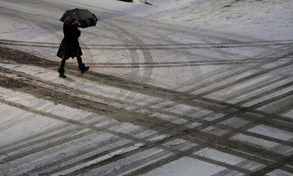 . A pedestrian walks across a snowy street in downtown Kansas City, Mo., on Saturday, Dec. 17, 2016. A winter storm of snow, freezing rain and bone-chilling temperatures hit the nation\'s mid-section and East Coast on Saturday. (AP Photo/Charlie Riedel)