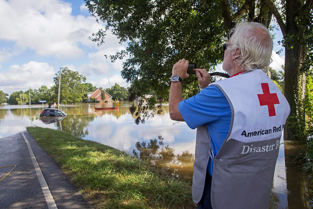 . James Hennessy, a Red Cross mental health volunteer from Tallahassee, Florida, takes a photo of Old Jefferson Highway which he was hoping to cross to reach Baton Rouge in Prairieville, La., Tuesday, Aug. 16, 2016. (AP Photo/Max Becherer)