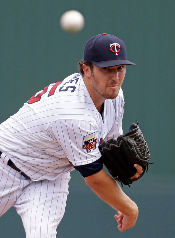 . Twins starting pitcher Phil Hughes throws in the first inning against the Red Sox. Hughes gave up four runs and 10 hits in 5-1/3 innings.  (AP Photo/Gerald Herbert)