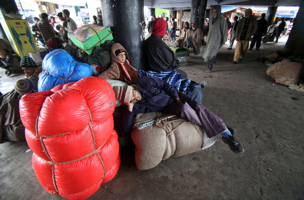 . Stranded passengers rest on luggage as they wait for the Jammu-Srinagar highway to reopen at a bus station in Jammu, India, Tuesday, Feb. 5, 2013. Following fresh snowfall and landslides in some areas, the Srinagar-Jammu highway remained closed for the second consecutive day Tuesday. (AP Photo/Channi Anand)