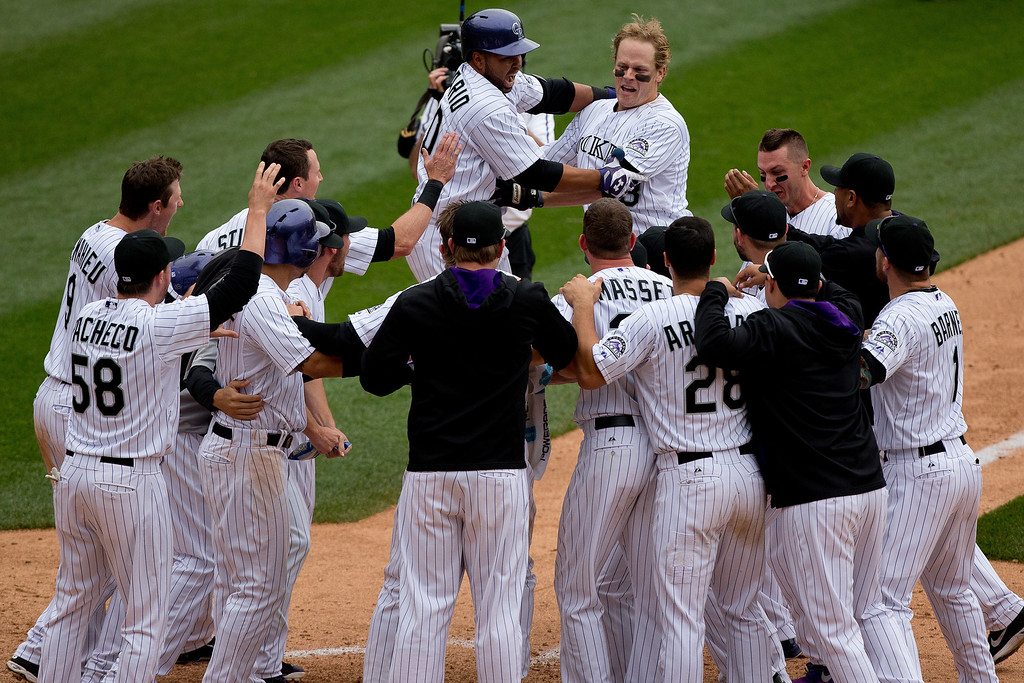 . Justin Morneau #33 of the Colorado Rockies is mobbed by teammates after hitting a walk off two-run home run in the 10th inning to defeat the San Diego Padres 8-6 at Coors Field on May 18, 2014 in Denver, Colorado. (Photo by Justin Edmonds/Getty Images)