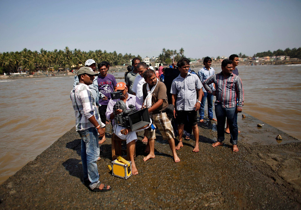""". A cinematographer films, as other members of the crew watch, during the shooting of Bollywood film \'Black Home\' at a beach on the outskirts of Mumbai April 26, 2013. Indian cinema marks 100 years since Dhundiraj Govind Phalke\'s black-and-white silent film \""""Raja Harishchandra\"""" (King Harishchandra) held audiences spellbound at its first public screening on May 3, 1913, in Mumbai. Indian cinema, with its subset of Bollywood for Hindi-language films, is now a billion-dollar industry that makes more than a thousand films a year in several languages. It is worth 112.4 billion rupees (over $2 billion) and leads the world in terms of films produced and tickets sold. Picture taken April 26, 2013. REUTERS/Danish Siddiqui"""
