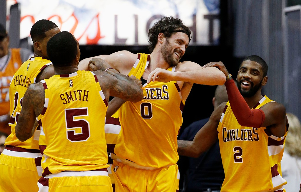 . Cleveland Cavaliers\' Kevin Love (0) smiles as he is helped up off the floor by teammates Kyrie Irving (2), J.R. Smith (5) and Tristan Thompson, left, during the first half of an NBA basketball game against the Phoenix Suns Monday, Dec. 28, 2015, in Phoenix. (AP Photo/Ross D. Franklin)