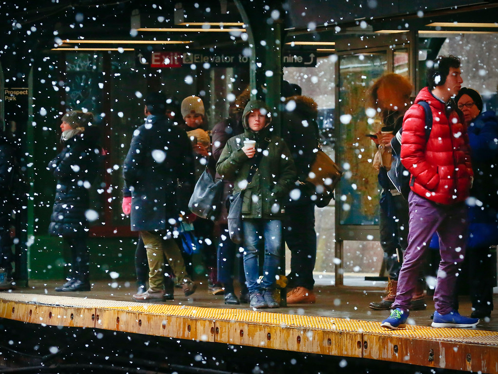 . Commuters are sheltered from snowfall while waiting on a subway platform, Tuesday March 13, 2018, in the Brooklyn borough of New York. The National Weather Service predicted between two and five inches of snow in the city and surrounding areas, where a winter weather advisory was in effect. (AP Photo/Bebeto Matthews)
