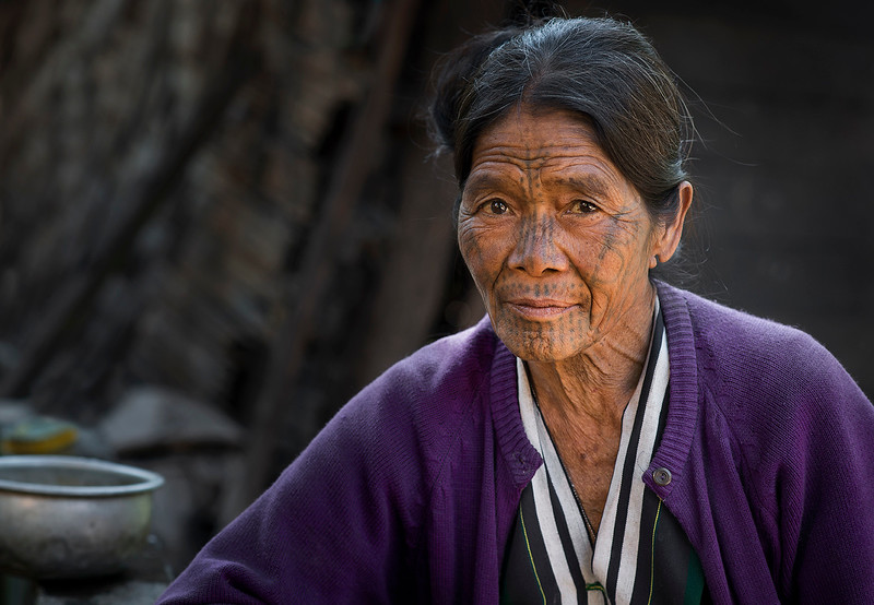 Tam Hlen is around 60 years old and had her face tattooed when she was 15. Although the design is a little faded out now it is still recognizable as the one worn by the women of the Muun tribe. Tan recalls the pain she went threw and remembers her mother being with her the whole time. Tam has 2 sons and 1 daughter and has lived in Ngait Kun village all her life.   Chin State, Myanmar,2017.