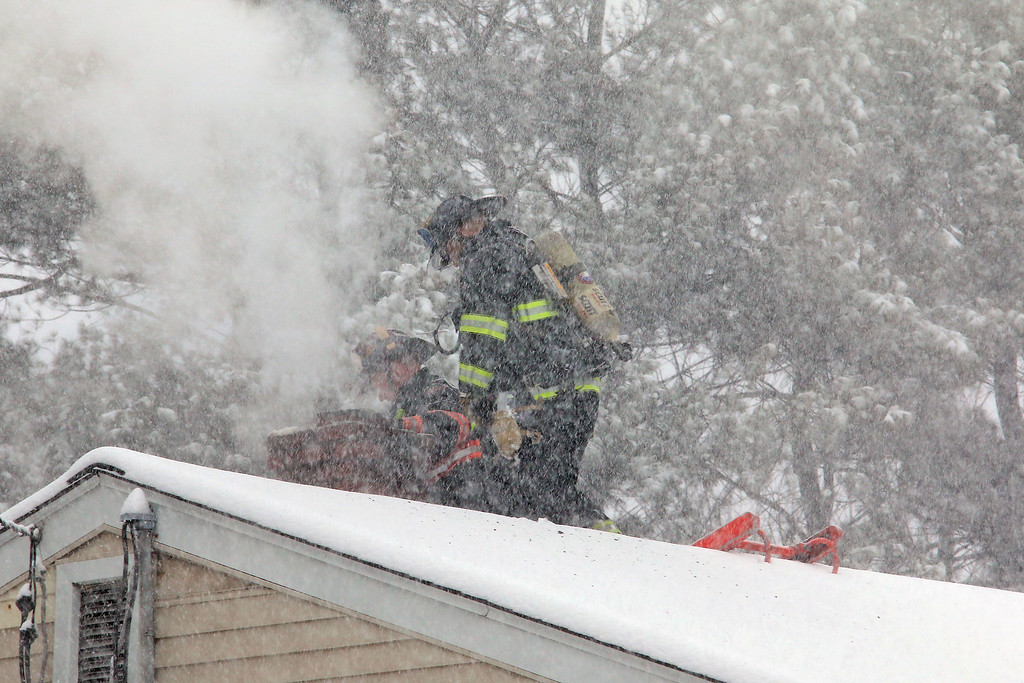 . Leominster Firefighters work on putting out a chimney fire on Mechanic Street in Leominster during the storm on Tuesday March 14, 2017. SENTINEL & ENTERPRISE/JOHN LOVE