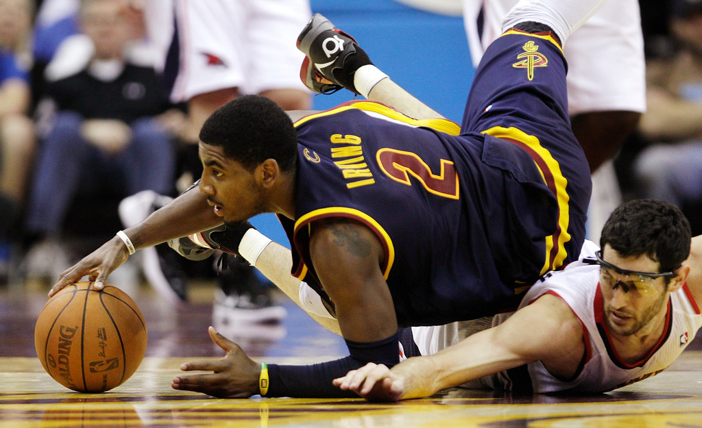 . Cleveland Cavaliers\' Kyrie Irving (2) flips over Atlanta Hawks\' Kirk Hinrich, right, as they chase a loose ball in the second half of an NBA basketball game in Cleveland on Sunday, March 18, 2012. The Hawks won 103-87. (AP Photo/Amy Sancetta)