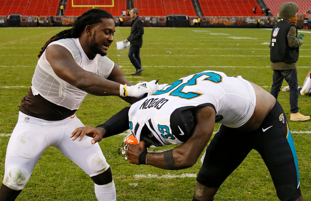 . Cleveland Browns running back Isaiah Crowell, left, pulls the jersey off Jacksonville Jaguars free safety Tashaun Gipson after an NFL football game, Sunday, Nov. 19, 2017, in Cleveland. (AP Photo/Ron Schwane)