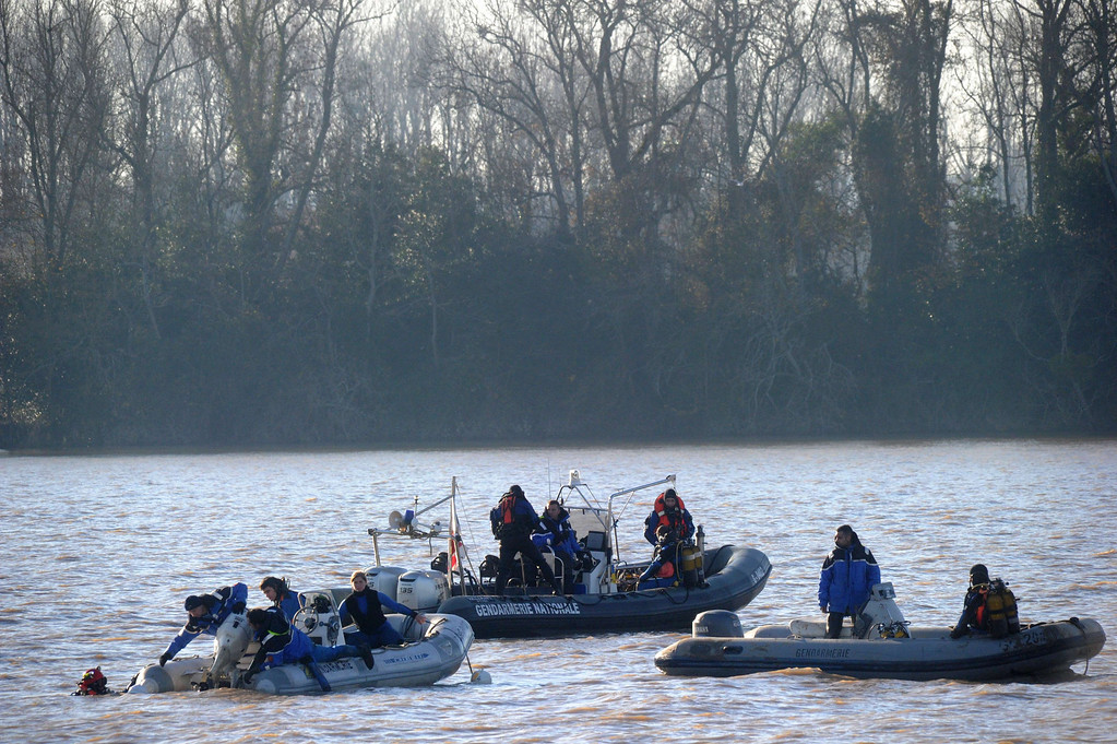 . Gendarmes take part on December 23, 2013  in Lugon-et-l\'Ile-du-Carnay, southwestern France, in an operation to lift a helicopter from the Dordogne river bed for clues into a crash that is thought to have killed a Chinese tycoon and a French winemaker.  AFP PHOTO / MEHDI FEDOUACH      load wreckages of the crashed Robinson R44 helicopter on a truck in Lugon-et-l\'Ile-du-Carnay, southwestern France, on December 23, 2013 after they lifted it from the Dordogne river bed. The crash, killing a Chinese tycoon, a French winemaker and an interpreter and financial advisor Peng Wang, occurred while they had been on a celebratory aerial tour of a chateau estate that Lam Kok, 46-year-old Chinese tea-and-property magnate, had just bought from James Gregoire, a French entrepreneur and the pilot of the helicopter. Only the body of Lam Kok\'s 12-year-old son Shun Yu Kok, has been recovered. AFP PHOTO / MEHDI FEDOUACHMEHDI FEDOUACH/AFP/Getty Images