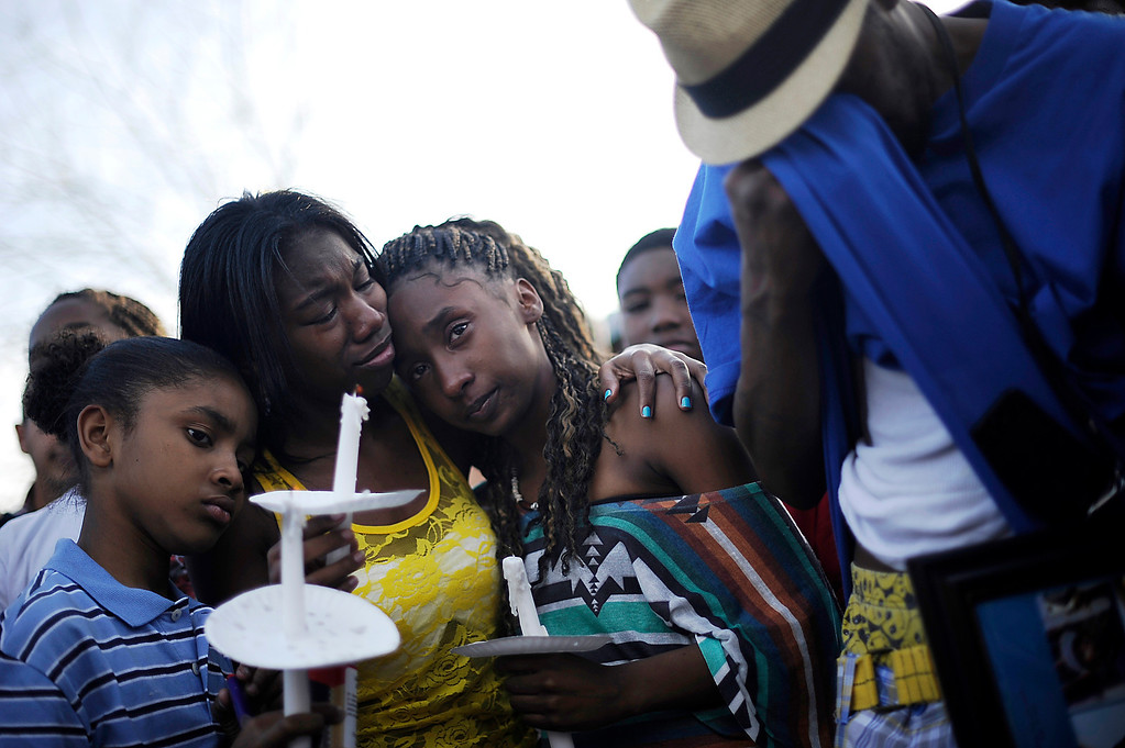 . Families attend a Peace Vigil for De\'Quan Walker-Smith by Fuller Park in Denver, Colo., on Saturday, March 24, 2012. From left, De\'Quan\'s cousin Zavier Martin, DeQuan\'s nieces Qiosha Smith and Ladeshadae Smith, and De\'Quan\'s elder brother Quincy. De\'Quan Walker-Smith was murdered March 19, 2012 north of Manual High School in Denver by someone who drove past him in a green Honda and then drove away. Hyoung Chang, The Denver Post