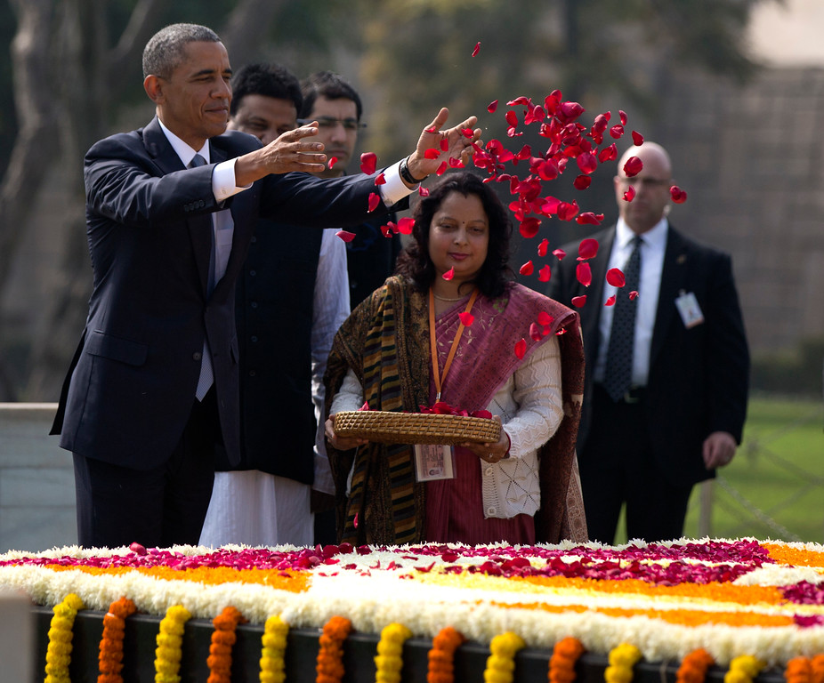 . President Barack Obama throws rose petals as he participates in a wreath laying ceremony at the Raj Ghat Mahatma Gandhi Memorial, New Delhi, India, Sunday, Jan. 25, 2015. Obama\'s arrival Sunday morning in the bustling capital of New Delhi marked the first time an American leader has visited India twice during his presidency. Obama is also the first to be invited to attend India\'s Republic Day festivities, which commence Monday and mark the anniversary of the enactment of the country\'s democratic constitution. (AP Photo/Carolyn Kaster)