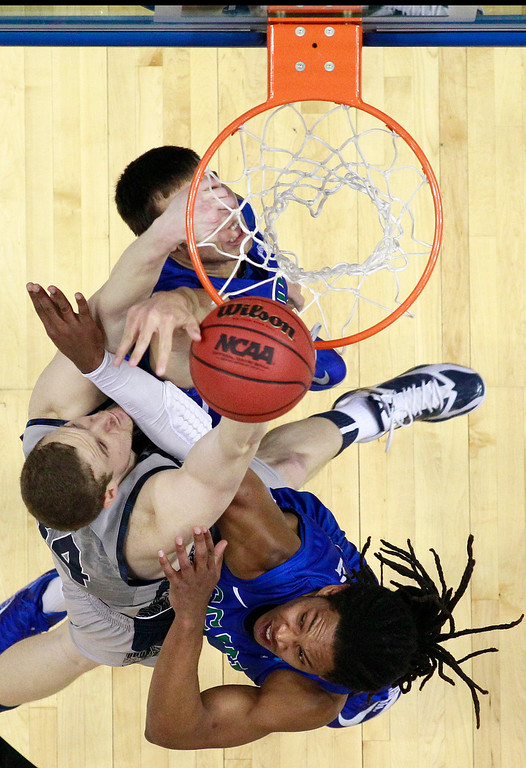 . Georgetown\'s Nate Lubick, left, tries to shoot past Florida Gulf Coast\'s Chase Fieler, top, and Sherwood Brown during the first half of a second-round game of the NCAA college basketball tournament on Friday, March 22, 2013, in Philadelphia. (AP Photo/Matt Rourke)