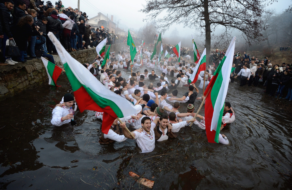 . People perform the national dance \'Horo\' holding national flags in the icy waters of the river in the town of Kalofer some 150 kms from Sofia, Bulgaria, 06 January 2014 during celebrations of the Epiphany day. Epiphany is a Christian feast that celebrates the arrival of the Three Wise Men with their gifts for the infant Jesus.  EPA/VASSIL DONEV