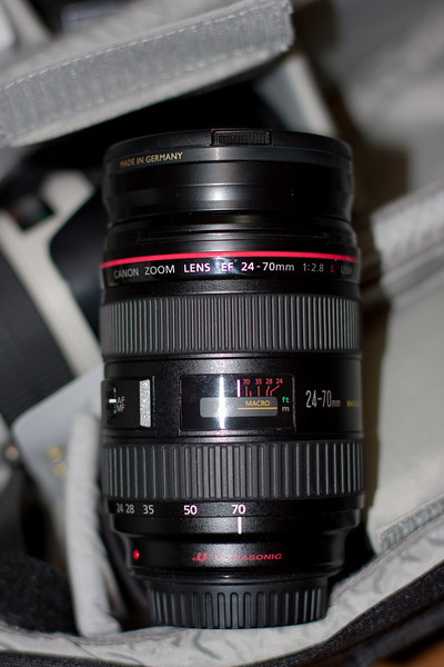 "The EF 24-70 f/2.8L, which is my current ""walkabout"" lens.  It covers an ideal focal length range for my crop camera, and the images it produces are incredibly sharp, even wide open.  Here it is shown zoomed all the way in, the barrel extends at the wide end.  This lens also does something magical with color and contrast - I get amazing contrast results right out of the camera.  Note the 77mm UV filter on the end.  The lens hood is not installed (but I usually use it in order to protect the lens)."