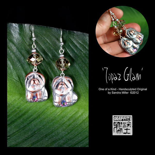 """TOPAZ GLAM EARRINGS  Faux silver and bronze shaded chows are hand sculpted from polymer clay to create a light as air pair of earrings!  The Topaz glass crystal the chows dangle from is a light catching magnet and the dogs feature a rose Swarovski crystal between their paws!!!!  Neutral in color and extremely versatile, these little chowlings can be dressed up or down according to your mood.    EARRINGS MEASURE 1 1/2"""" long x 3/4"""" wide without wire"""