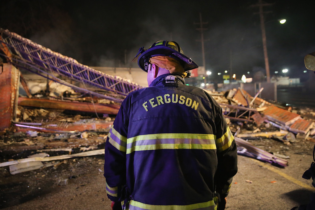 . A Ferguson firefighter surveys rubble at a strip mall that was set on fire when rioting erupted following the grand jury announcement in the Michael Brown case on November 25, 2014 in Ferguson, Missouri. Brown, an 18-year-old black man, was killed by Darren Wilson, a white Ferguson police officer, on August 9. At least 12 buildings were torched and more than 50 people were arrested during the night-long rioting.  (Photo by Scott Olson/Getty Images)