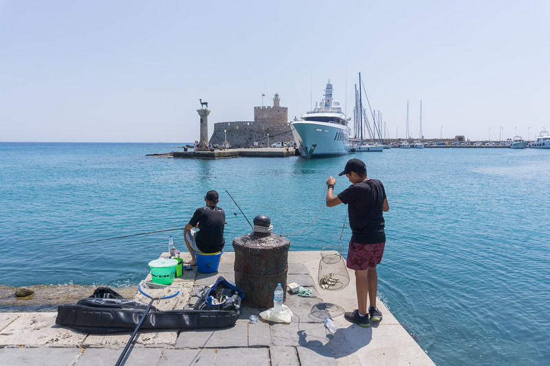 June 2019 - Rhodes, Greece - Fisherman in Old Town Harbour