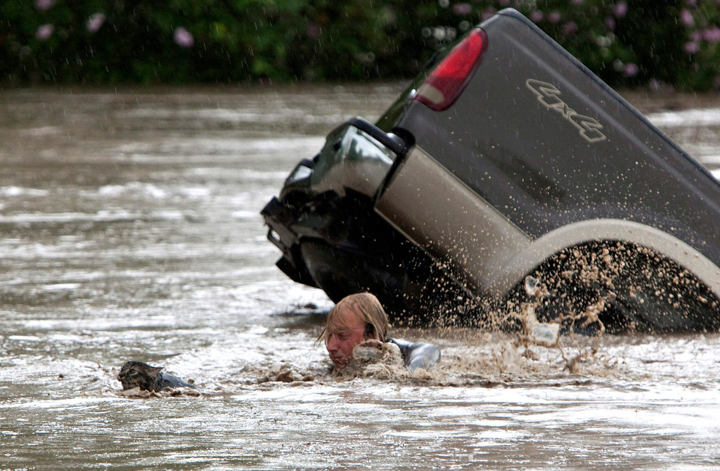 . Kevan Yaets swims after his cat Momo to safety as the flood waters sweep him downstream after submerging his truck in High River, Alberta on Thursday, June 20, 2013 after the Highwood River overflowed its banks. Hundreds of people have been evacuated with volunteers and emergency crews helping to aid stranded residents. (AP Photo/The Canadian Press, Jordan Verlage)