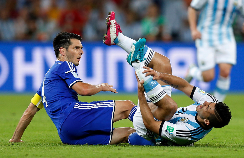 . Argentina\'s Sergio Aguero, right, holds his shin after being fouled during the group F World Cup soccer match between Argentina and Bosnia at the Maracana Stadium in Rio de Janeiro, Brazil, Sunday, June 15, 2014.  (AP Photo/Victor R. Caivano)