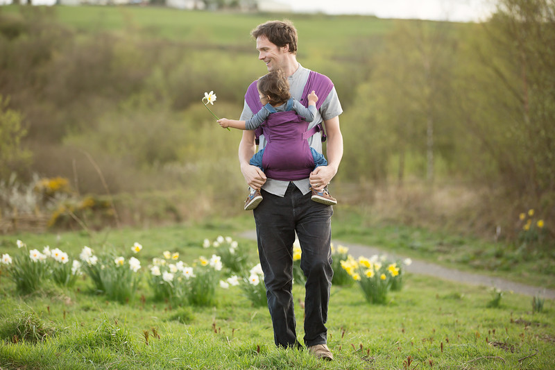 Izmi_Baby_Carrier_Cotton_Midnight_Purple_Lifestyle_Front_Child_Holding_Flower.jpg