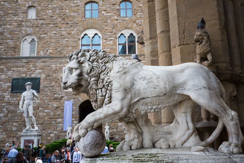 A Medici lion (Vacca, c. 1598) at the entrance to the Loggia dei Lanzi, with the copy of David in the background.