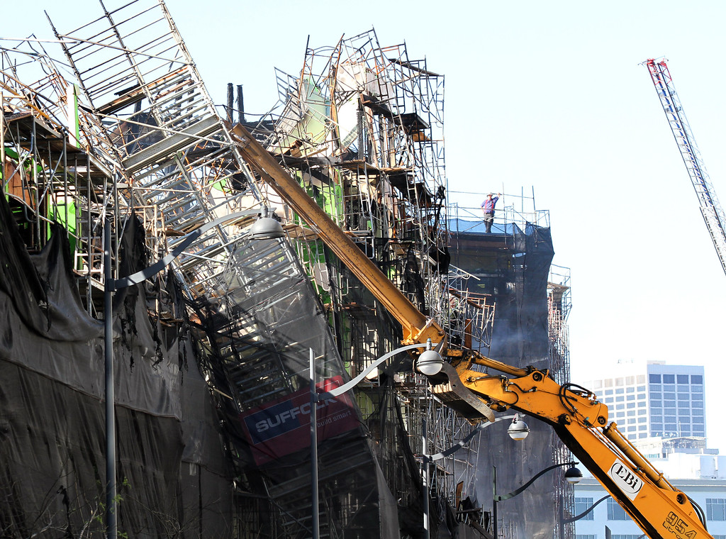 . Workers with the construction company Suffolk begin tearing down the structure that is left after a massive fire destroyed most of the structure in the Mission Bay neighborhood in San Francisco, Calif., on Wednesday, March 12, 2014. (Laura A. Oda/Bay Area News Group)
