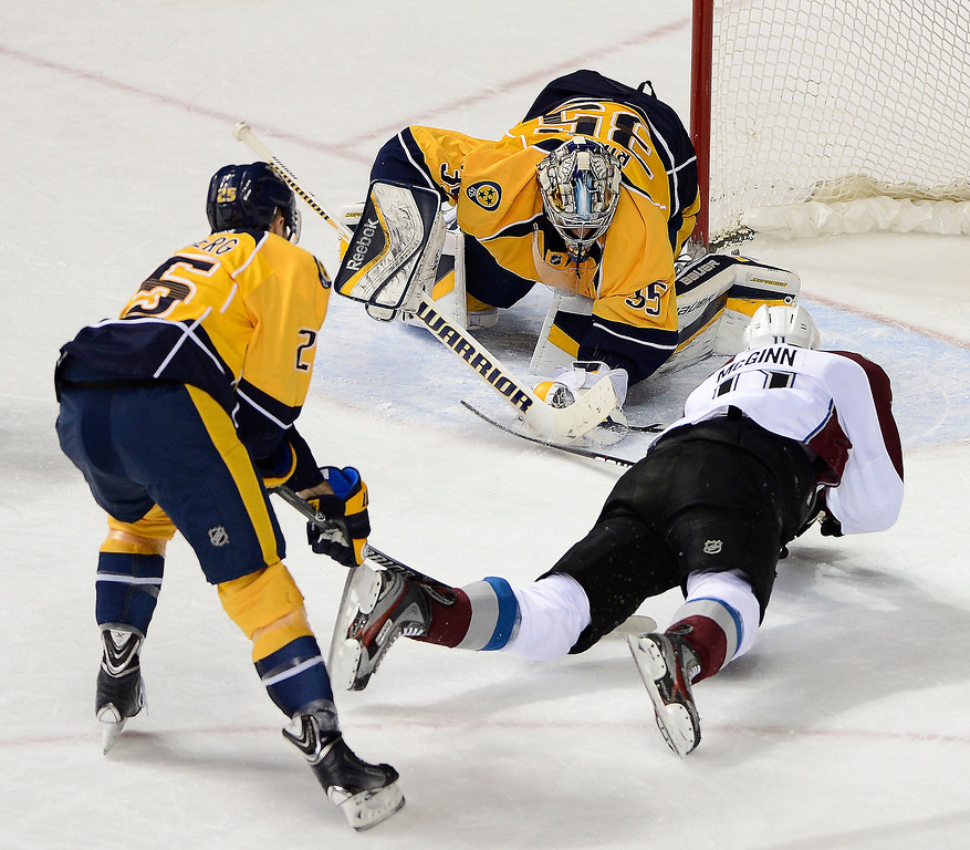 . Nashville Predators goalie Pekka Rinne (35), of Finland,  gloves a shot by Colorado Avalanche left wing Jamie McGinn (11) as he is defended by forward Viktor Stalberg (25), of Sweden, in the second period of an NHL hockey game on Tuesday, March 25, 2014, in Nashville, Tenn. (AP Photo/Mark Zaleski)