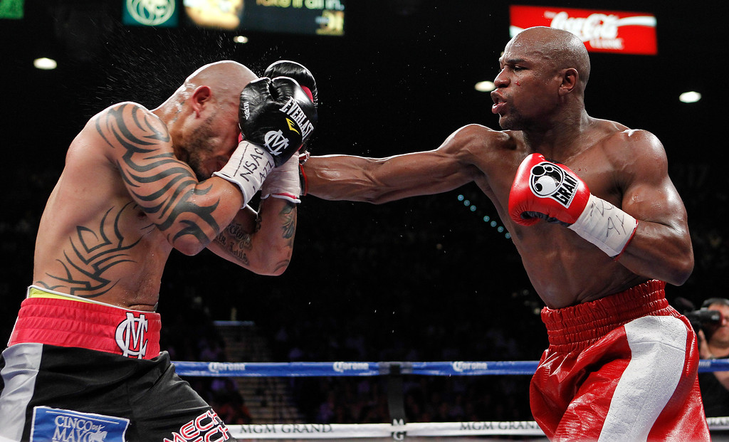 . Floyd Mayweather Jr., right, lands a punch against Miguel Cotto during a WBA super welterweight title fight, Saturday, May 5, 2012, in Las Vegas.  (AP Photo/Isaac Brekken)