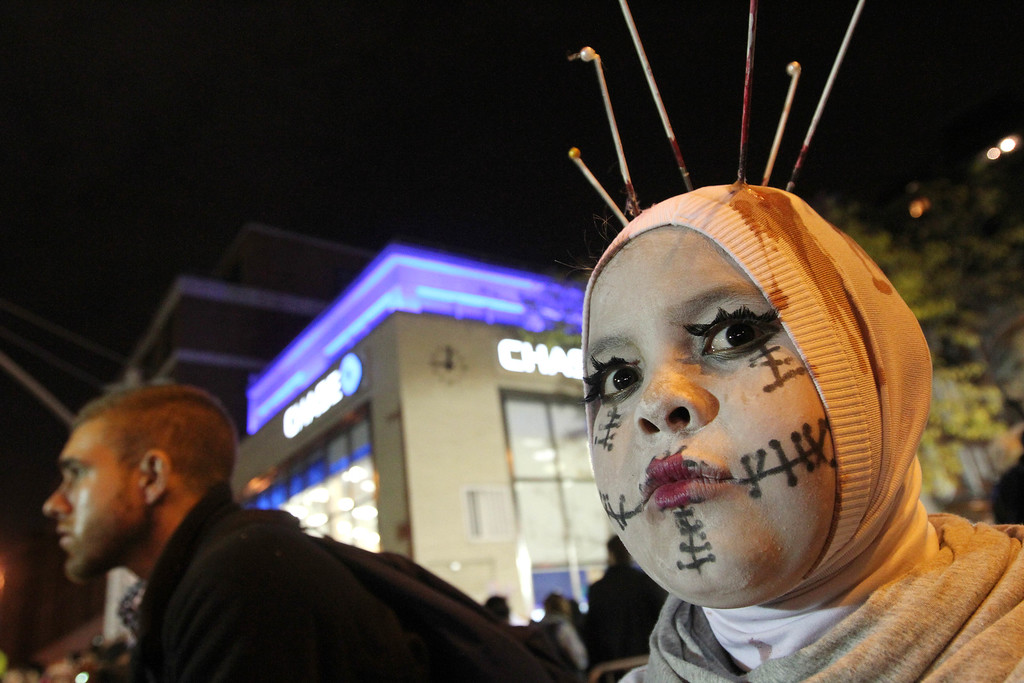 . A costumed Azriel Fernandez, 11, right, poses for a photograph as he watches the Village Halloween Parade make its way up New York\'s Sixth Avenue on Thursday, Oct. 31, 2013. (AP Photo/Tina Fineberg)