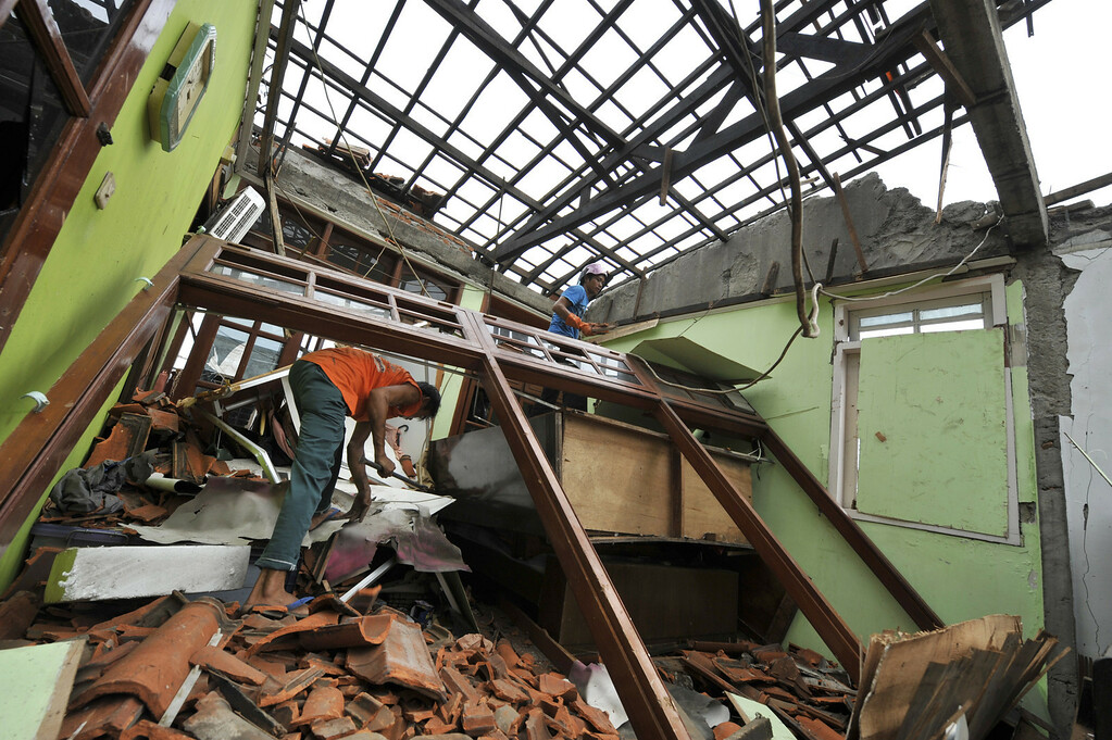 . Workers clean up debris from the bedroom of a two-story residence after being hit by a meteor, located in Delima street, eastern Jakarta on May 4, 2010. Following investigations by the Indonesian National Aeronautics and Space Agency and police forensic teams, it was concluded on May 3, that the incident was a meteorological accident and the explosion was caused by a meteor. The owner Soedarmojo and his wife were away when the meteor\'s impact heavily damaged the house and two adjoining residences at 4.30 in the afternoon (0930 GMT) of April 29, 2010. Authorities said they are still searching for meteorite pieces in the rubble and advised the community to surrender any meteorite pieces they find.  ROMEO GACAD/AFP/Getty Images
