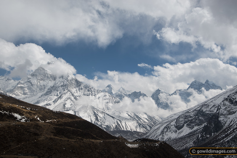 Afternoon cloud swirls over Ama Dablam (L) and Kangtega (R). In the foreground, the trail splits - uphill to Dingboche, and lower trail to Pheriche, which is just visible at the end of the valley.