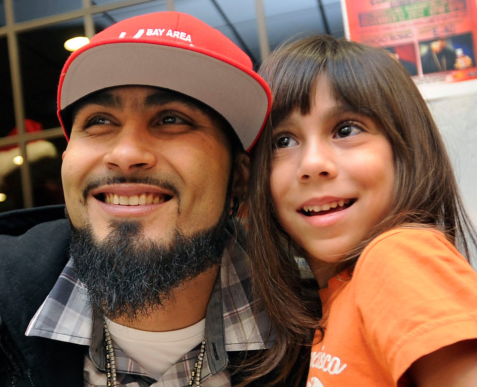 . Monica Minyen, 6, of Pleasant Hill, moves in close as her father Richard Minyen takes her photograph with Giants reliever Sergio Romo at Kinders Meat and Deli on Wednesday, Dec. 12,  2012, in Pleasant Hill, Calif. Romo teamed up with rapper E-40 and Marine Corps Reserve Toys for Tots collecting a toy in exchange for an autograph with the two celebrities. (Susan Tripp Pollard/Staff)