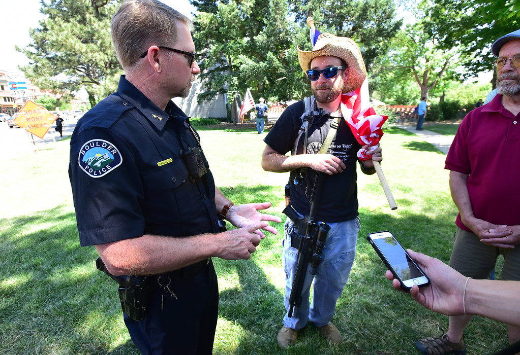 . Deputy Chief Carey Weinheimer, left, responds to Jason Boros\' questions abut the new regulations regarding firearms which includes a ban on the sale and possession of assault weapons during a Second Amendment rally in Boulder on Saturday. For more photos and video go to dailycamera.com. Paul Aiken Staff Photographer