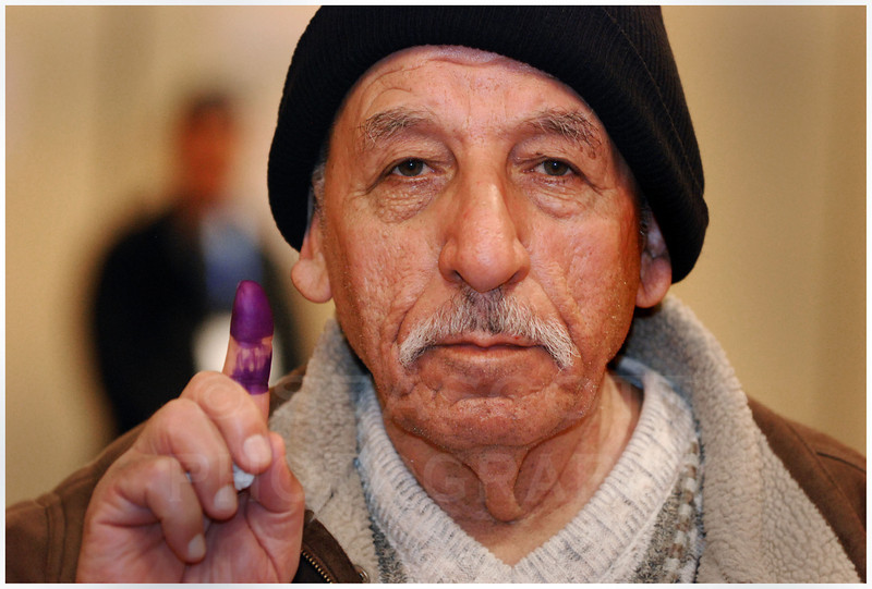 In Warren, Michigan, after voting in the Iraqi national election, a man holds up his ink stained finger to show he's cast his ballot.