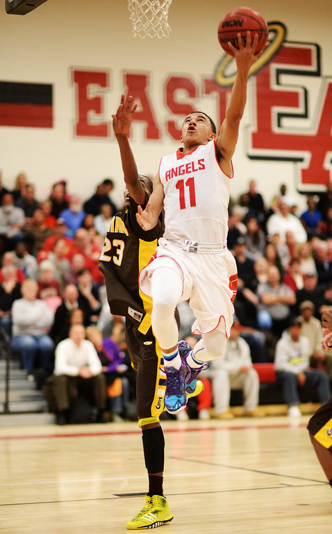 . DENVER, CO. JANUARY 24: Brain Carey of East High School (11) makes a basket ahead of Josh McNair of Thomas Jefferson High School (23) in the 2nd half of the game at East High School in Denver, Colorado January 24, 2014. East High School won 91-62. (Photo by Hyoung Chang/The Denver Post)