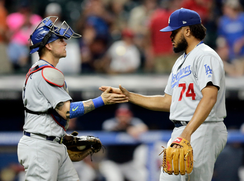 . Los Angeles Dodgers relief pitcher Kenley Jansen, right, is congratulated by catcher Yasmani Grandal after the Dodgers defeated the Cleveland Indians 7-5 in a baseball game, Tuesday, June 13, 2017, in Cleveland. (AP Photo/Tony Dejak)